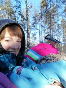 A woman dressed for winter smiles at the camera, holding a baby with a chickadee on its head